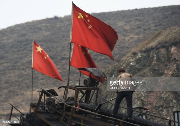 ChinaeconomyenvironmentcoalclimateFOCUS by Tom HANCOCK In this photo taken on November 20 Chinese flags fly as a worker clearing a conveyer belt used...
