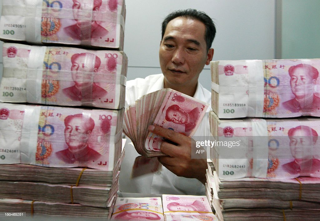 China-economy-forex,FOCUS BY KELLY OLSEN This picture taken on August 17, 2012 shows a Chinese bank staff member counting stacks of 100-yuan notes at a bank in Huaibei, east China's Anhui province. China's currency is facing strong downward pressure this year as the country's once surging growth rates slow amid a stalling global economy and signs of capital flight after years of inflows. CHINA