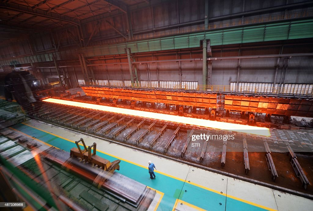 Chinaeconomymanufacturinggrowthsocial FOCUS by Tom Hancock This picture taken on April 11 2015 shows a Chinese worker at a steel mill in Tangshan...