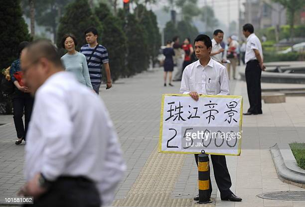 ChinaeconomypropertyFOCUS BY Fran Wang A real estate agent holds a placard showing the housing price along a street in Beijing on May 16 2010...