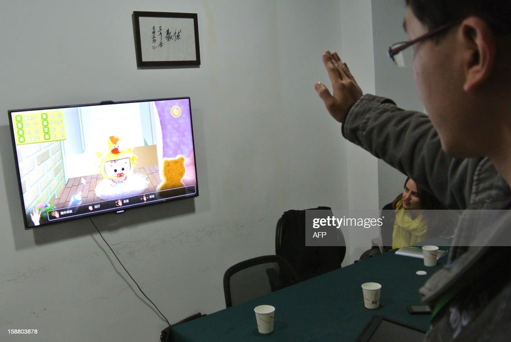 China-economy-technology,FOCUS BY SEBASTIEN BLANC This photo taken on December 12, 2012 shows a developer testing a game for children in an office in Chengdu, southwest China's Sichuan province. Moving his hand in front of a television to test motion, a developer of GoodTeam presents the start-up of his latest creation: a catching game to put a bottle in a baby's mouth. Entrepreneurs in China's southwest are dreaming of turning the city of Chengdu into the world's next Silicon Valley as the government encourages more investment outside the already booming coastal regions. AFP PHOTO / SEBASTIEN BLANC