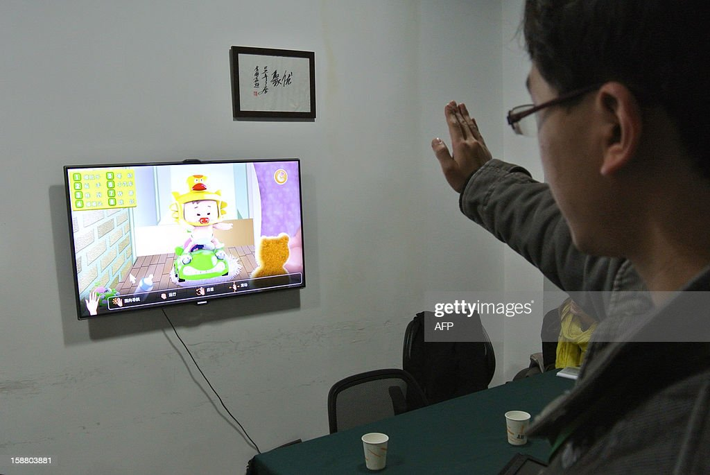 China-economy-technology,FOCUS BY SEBASTIEN BLANC This photo taken on December 12, 2012 shows a developer testing a game for children in an office in Chengdu, southwest China's Sichuan province. Moving his hand in front of a television to test motion, a developer of GoodTeam presents the start-up of his latest creation: a catching game to put a bottle in a baby's mouth. Entrepreneurs in China's southwest are dreaming of turning the city of Chengdu into the world's next Silicon Valley as the government encourages more investment outside the already booming coastal regions.