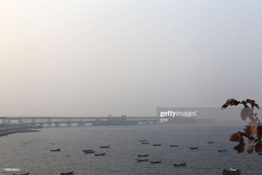 WITH 'China-environment-health-unrest' by Carol Huang Boats berth in the waters near the faculties of Fujia Dahua factory, which was ordered to halt work and relocate 17 months ago, in Dalian, northeast China's Liaoning province on January 18, 2013. Clouds of smoke billow from the chimneys at a Chinese chemical plant rumbling with activity, more than a year after authorities closed it following protests by thousands of people. CHINA OUT AFP PHOTO