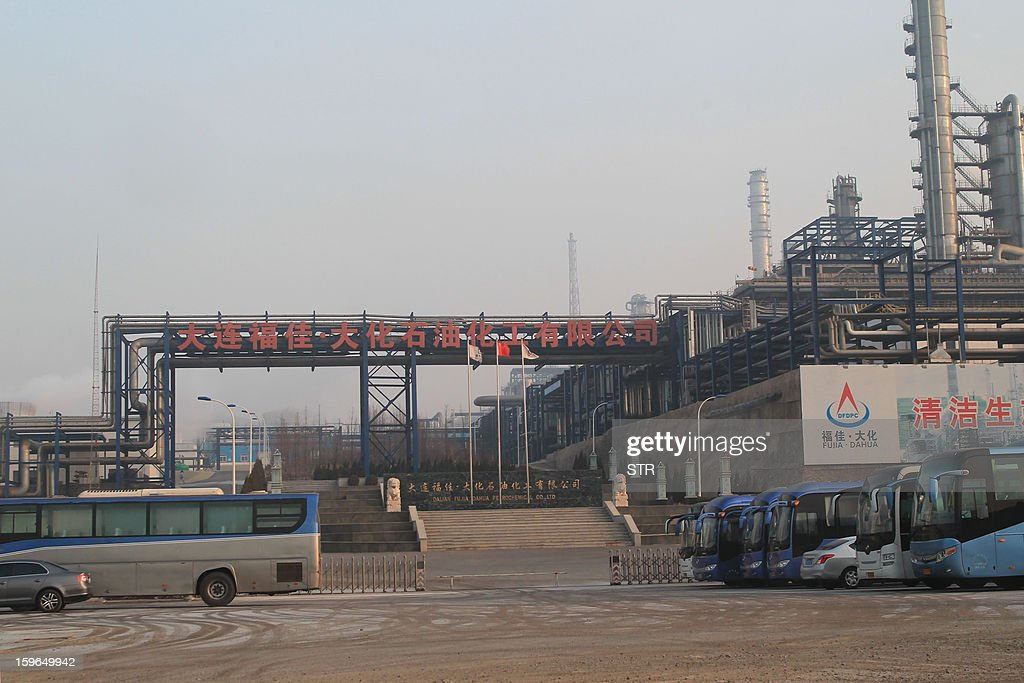 WITH 'China-environment-health-unrest' by Carol Huang Buses stop at the gate of Fujia Dahua factory, which was ordered to halt work and relocate 17 months ago, in Dalian, northeast China's Liaoning province on January 18, 2013. Clouds of smoke billow from the chimneys at a Chinese chemical plant rumbling with activity, more than a year after authorities closed it following protests by thousands of people. CHINA