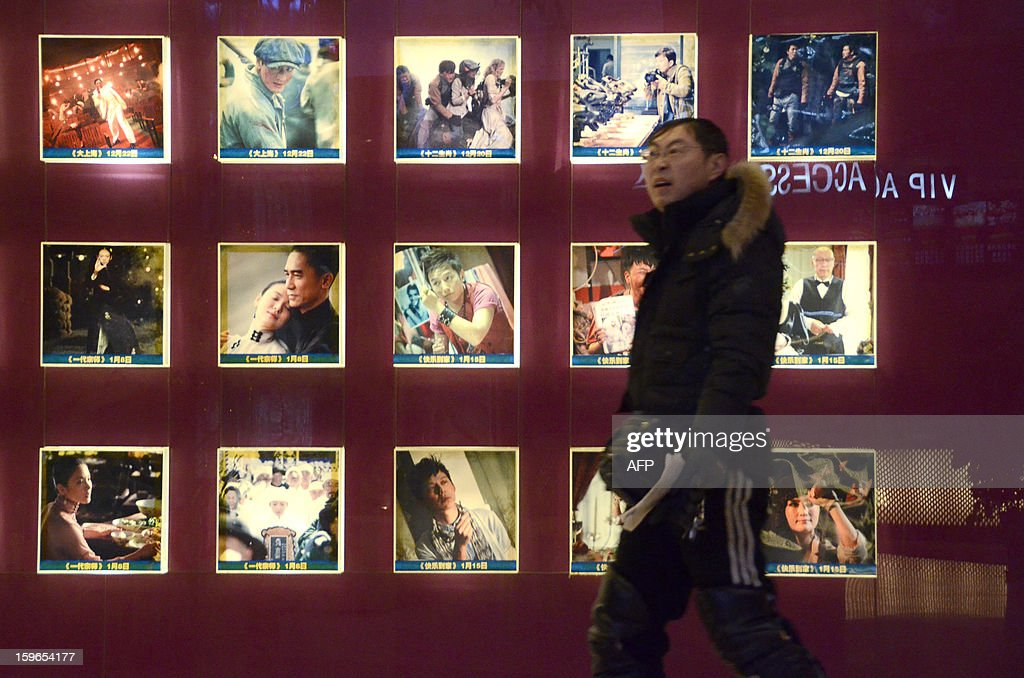 China-film-entertainment,FOCUS by Sebastien Blanc A Chinese man walks past a set of illuminated movie posters at a cinema in Beijing on January 18, 2013. Ten new movie screens open each day in China as the popularity of cinema soars in the country, but the appeal of Chinese films has failed to maintain the pace.