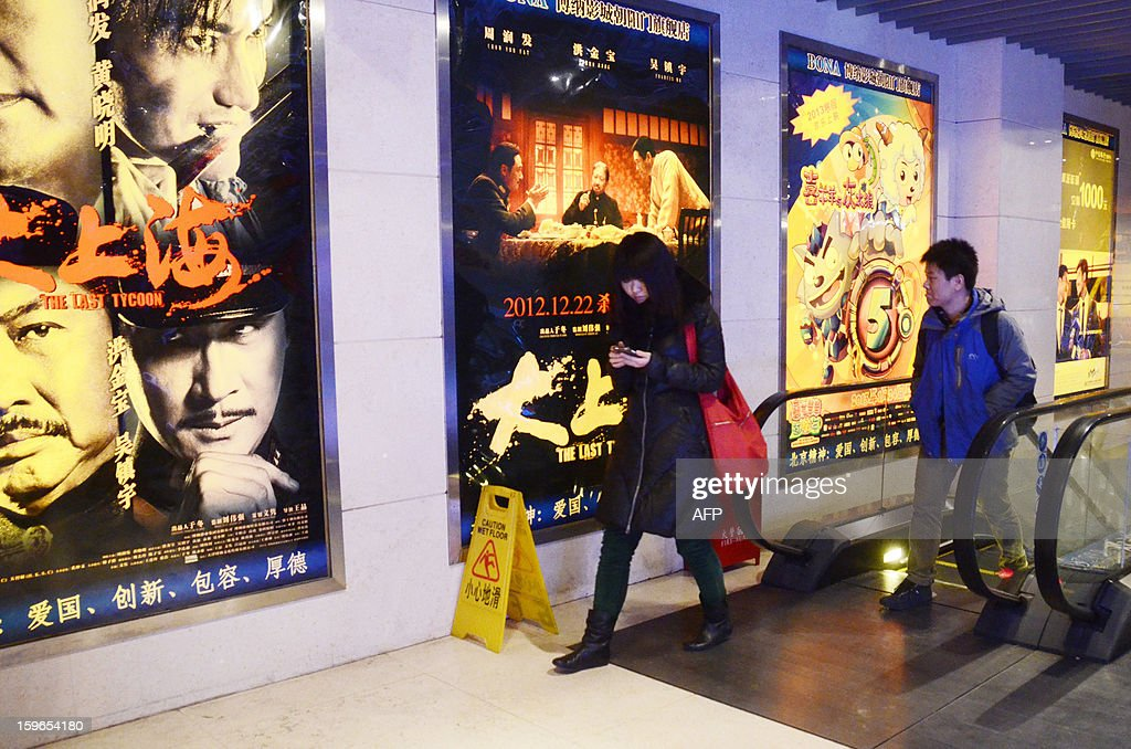 China-film-entertainment,FOCUS by Sebastien Blanc A Chinese woman (L) walks past film advertisements at a cinema in Beijing on January 18, 2013. Ten new movie screens open each day in China as the popularity of cinema soars in the country, but the appeal of Chinese films has failed to maintain the pace.