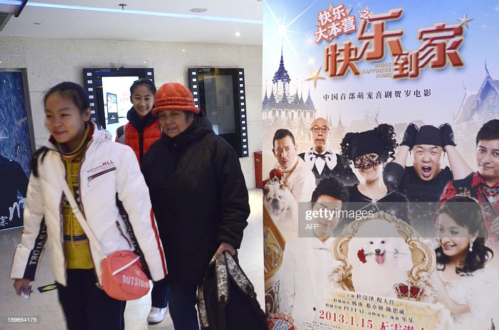 China-film-entertainment,FOCUS by Sebastien Blanc People walk past a film poster after buying tickets at a cinema in Beijing on January 18, 2013. Ten new movie screens open each day in China as the popularity of cinema soars in the country, but the appeal of Chinese films has failed to maintain the pace.