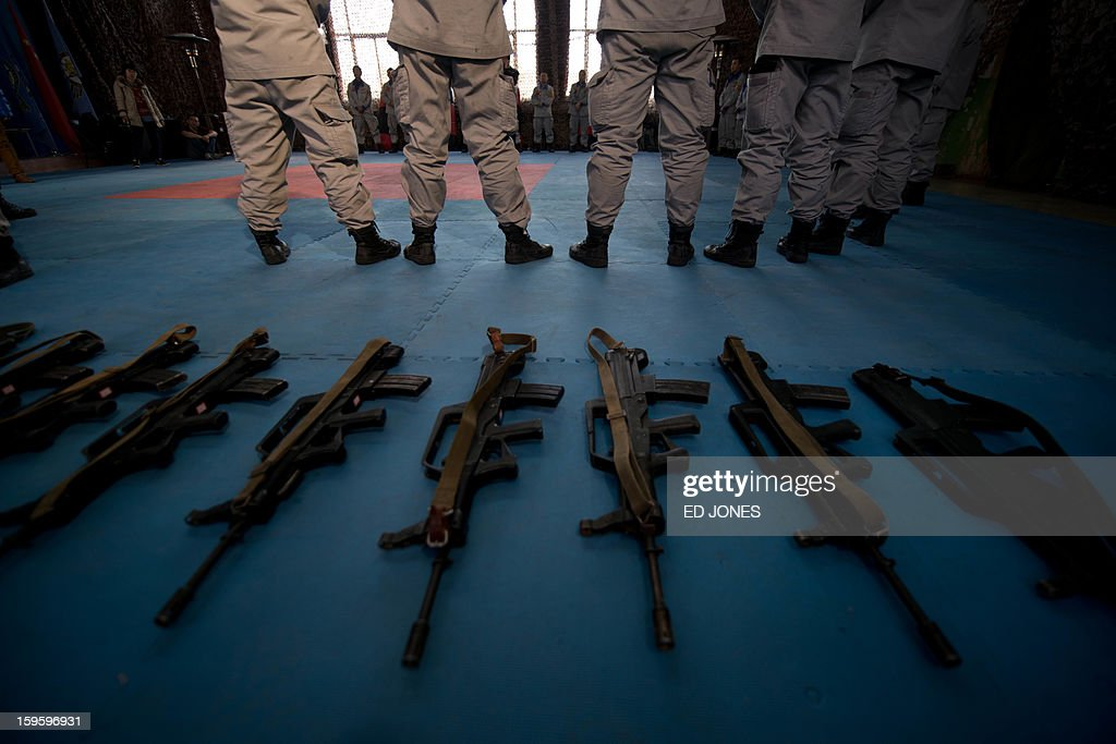 STORY 'China-military-security-politics,FEATURE' by Tom Hancock Assault rifles lie at the feet of bodyguard trainees at the Genghis Security Academy in Beijing on January 17, 2013. In sub-zero winter cold, trainees at an army base outside Beijing wake before dawn to practise martial arts and evasive driving, under the instruction of a Portuguese ex-special forces soldier. The roughly 40-strong group -- mostly with previous military experience -- are on a commercial training course to become elite bodyguards protecting Chinese firms as they seek ever more resources and contracts in some of the world's most unstable regions. AFP PHOTO / Ed Jones