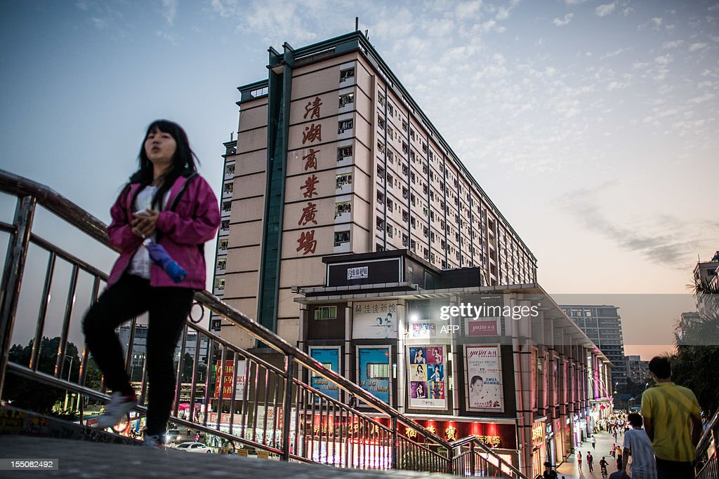 China-party-congress-economy-workers,FOCUS by Robert Saiget This picture taken on October 31, 2012 shows an employee of Taiwanese electronics manufacturer Foxconn walking the stairs of a pedestrian brigde leading to commercial and residential buildings in the area of the company's compound in Shenzhen. The factories that have powered China's economic miracle are reeling from the global slowdown, presenting the incoming leadership in Beijing with a restless workforce at a defining moment in the country's growth story. AFP PHOTO
