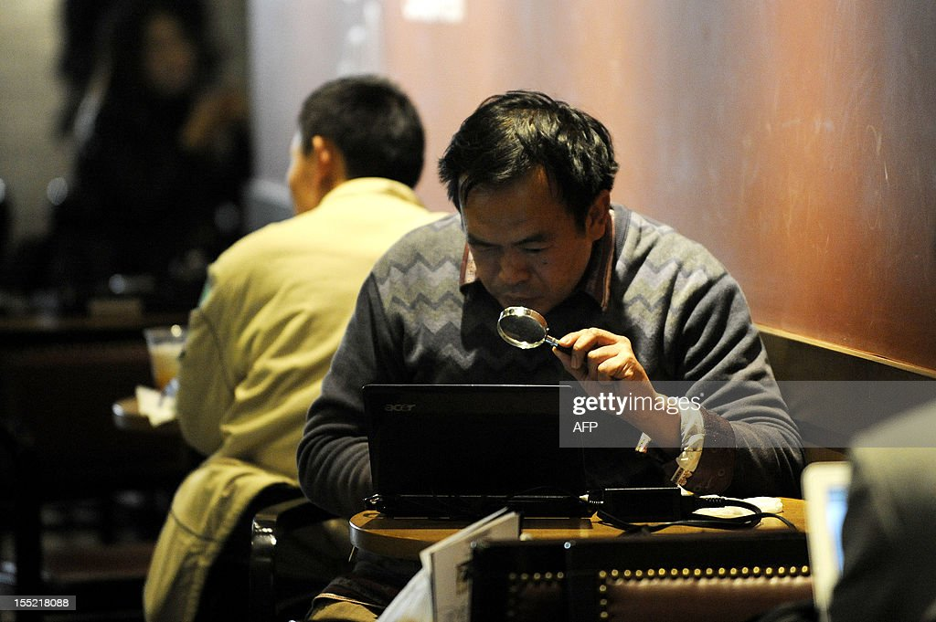 China-politics-congress-Internet,FOCUS by Tom Hancock A man looks at his laptop computer with a magnifying glass at a cafe in Beijing on November 2, 2012. China has witnessed explosive growth in Internet usage since the last Communist Party transition in 2002, with the online community of 538 million posing a huge challenge to the party's attempts to shape public opinion. AFP PHOTO / WANG ZHAO