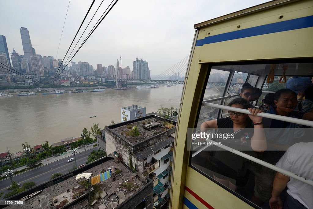 WITH 'China-politics-corruption-Bo,ADVANCER' BY This photo taken on August 9, 2013 shows the sweeping views of Chongqing's high-rise city centre and a cable car across the Yangste River. In a plot worthy of a spy novel, the downfall of high-flying Chinese politician Bo Xilai began when a British businessman was found dead in a hilltop hotel room in this metropolis of over 25 million people and now Bo, once one of China's highest-flying politicians, will find himself in a criminal dock on August 22 on trial for bribery and abuse of power in the country's highest-profile prosecution in decades. AFP PHOTO/Peter PARKS