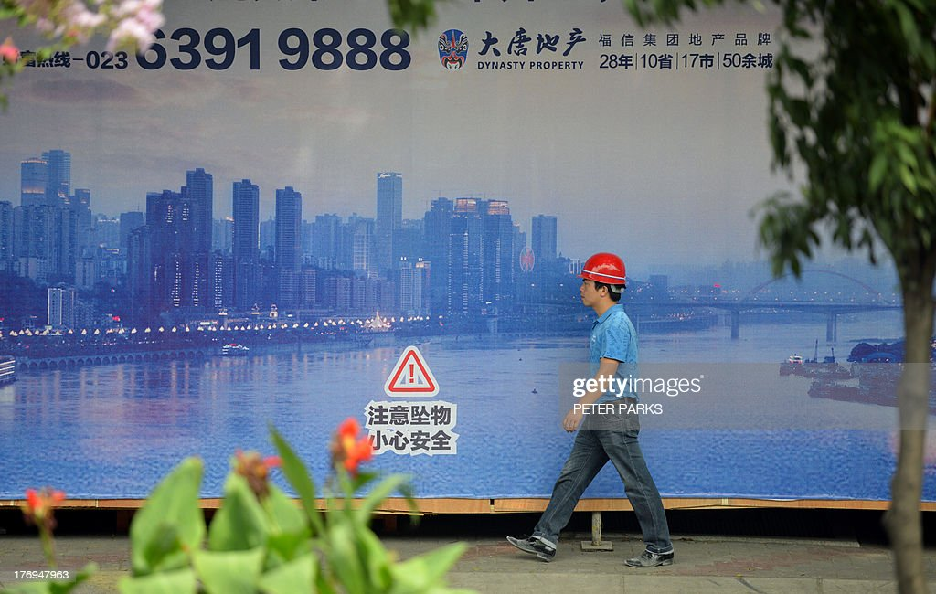 WITH 'China-politics-corruption-Bo,ADVANCER' BY This photo taken on August 8, 2013 shows a construction worker passing a poster of the sweeping views of Chongqing's high-rise city centre across the Yangste River. In a plot worthy of a spy novel, the downfall of high-flying Chinese politician Bo Xilai began when a British businessman was found dead in a hilltop hotel room in this metropolis of over 25 million people and now Bo, once one of China's highest-flying politicians, will find himself in a criminal dock on August 22 on trial for bribery and abuse of power in the country's highest-profile prosecution in decades. AFP PHOTO/Peter PARKS