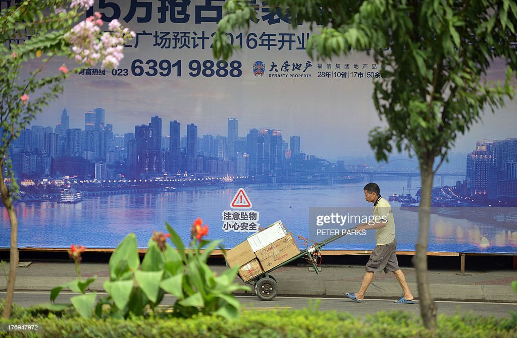 WITH 'China-politics-corruption-Bo,ADVANCER' BY This photo taken on August 8, 2013 shows a worker passing a poster of the sweeping views of Chongqing's high-rise city centre across the Yangste River. In a plot worthy of a spy novel, the downfall of high-flying Chinese politician Bo Xilai began when a British businessman was found dead in a hilltop hotel room in this metropolis of over 25 million people and now Bo, once one of China's highest-flying politicians, will find himself in a criminal dock on August 22 on trial for bribery and abuse of power in the country's highest-profile prosecution in decades. AFP PHOTO/Peter PARKS