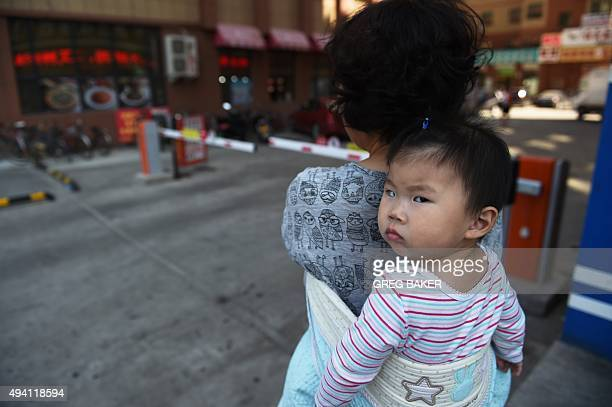 Chinapoliticseconomy FOCUS by Benjamin DOOLEY This photo taken on June 24 2015 shows a woman carrying a baby in Yanji in China's northeast Jilin...