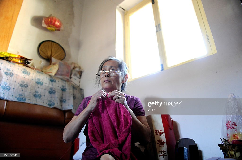 China-population-social-family,FEATURE BY CAROL HUANG This picture taken on September 4, 2012 shows Wu Rui knitting a sweater during an interview at her home in Beijing. When Wu Rui's 12-year-old daughter died she lost not just the only child she would ever have but also her source of security and support in old age.
