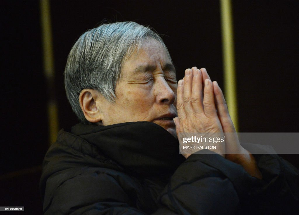 China-religion-Vatican-Catholic-pope,FOCUS by Kelly Olsen This photo taken on on February 20, 2013 shows a Chinese Catholic praying at the Cathedral of the Immaculate Conception in Beijing. Experts estimate that there are as many as 12 million Catholics in China, with about half in congregations under the officially-administered Chinese Catholic Patriotic Association. The rest belong to non-sanctioned or so-called underground churches, though despite the name many operate in the open, with experts saying levels of acceptance depend on local officials' attitudes. AFP PHOTO / Mark RALSTON