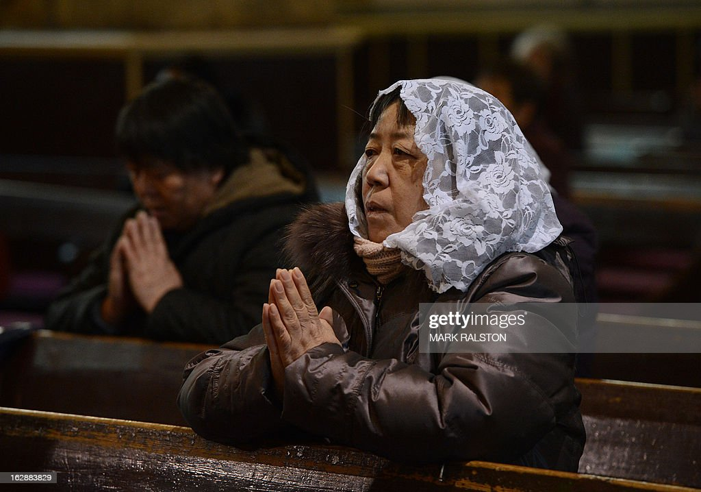 China-religion-Vatican-Catholic-pope,FOCUS by Kelly Olsen This photo taken on on February 20, 2013 shows Chinese Catholics praying at the Cathedral of the Immaculate Conception in Beijing. Experts estimate that there are as many as 12 million Catholics in China, with about half in congregations under the officially-administered Chinese Catholic Patriotic Association. The rest belong to non-sanctioned or so-called underground churches, though despite the name many operate in the open, with experts saying levels of acceptance depend on local officials' attitudes. AFP PHOTO / Mark RALSTON