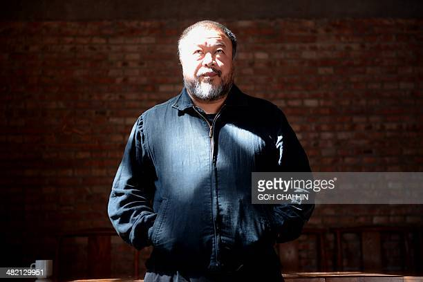 China's best known and boldest contemporary artist Ai Weiwei poses at his studio in the suburbs of Beijing on April 3 2014 The biggestever exhibition...