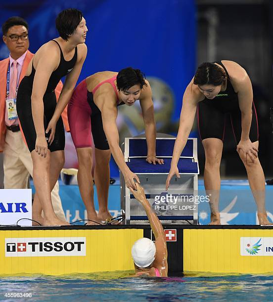 China's Cao Yue Guo Junjun and Tang Yi congratulate final lap swimmer Shen Duo after their victory in the final for the women's 4 x 200m freestyle...