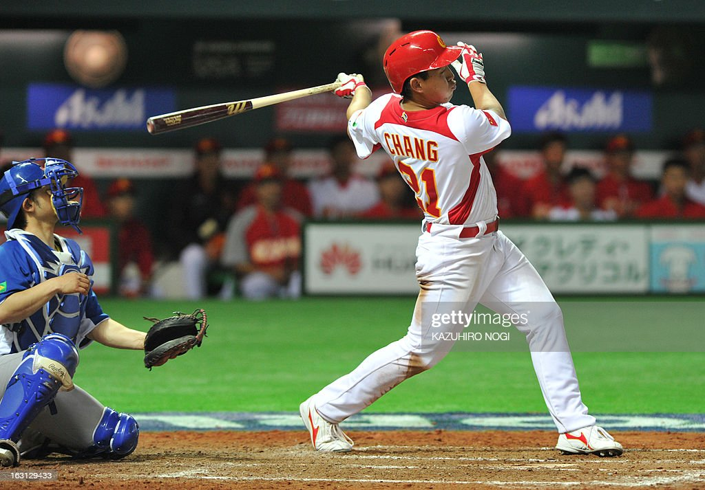 China's Chang Ray (R) bats a single as Brazil's catcher Diego Franca (L) looks on during the eighth inning of their first-round Pool A game in the World Baseball Classic tournament in Fukuoka on March 5, 2013. China beat Brazil 5-2. AFP PHOTO / KAZUHIRO NOGI