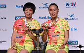 China's Chen Quingchen and Bao Yixin pose for photos with the winner's trophy and their medals after their victory in the women's doubles final...