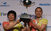 China's Chen Quingchen and Bao Yixin pose for photos with the winner's trophy after their victory in the women's doubles final against Indonesia's...
