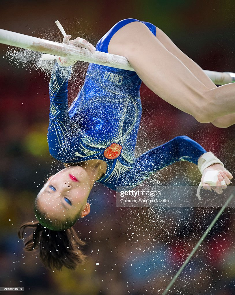 China's Chunsong Shang hangs upside down to chalk the bars before competing on Sunday Aug 14 2016 at the Rio Games Shang placed fifth in the event