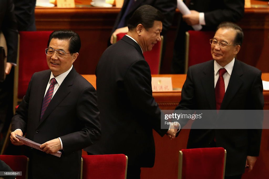 China's Communist Party Chief Xi Jinping (C) shakes hands with China's Premier Wen Jiabao (R) as China's President Hu Jintao (L) leaving after the opening session of the Chinese People's Political Consultative Conference in Beijing's Great Hall of the People on March 3, 2013 in Beijing, China.