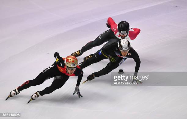 China's Dajing Wu Japan's Keita Watanabe and Canada's Charles Hamelin compete during the final competition in the 'Men 5000m Relay' category at the...
