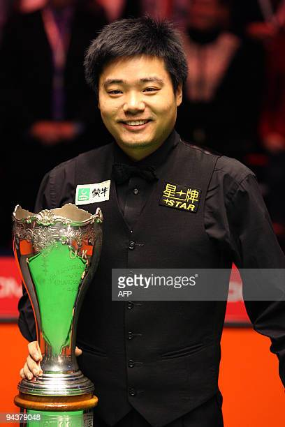 China's Ding Junhui celebrates with the trophy after defeating Scotland's John Higgins in the snooker UK Championship in Telford central England on...