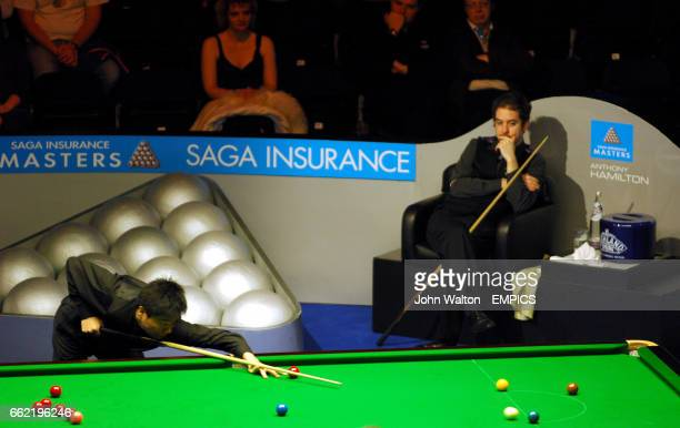 China's Ding Junhui is watched over by Anthony Hamilton as he pots the green