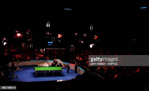 China's Ding Junhui is watched over by Anthony Hamilton