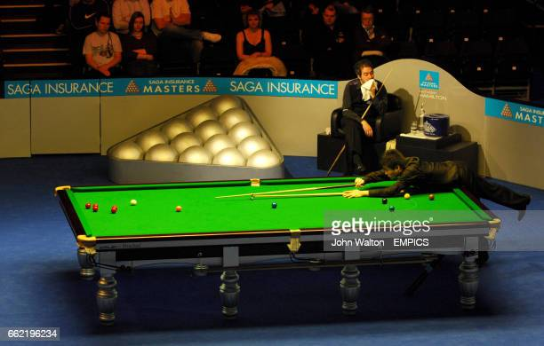 China's Ding Junhui plays a long red watched over by Anthony Hamilton