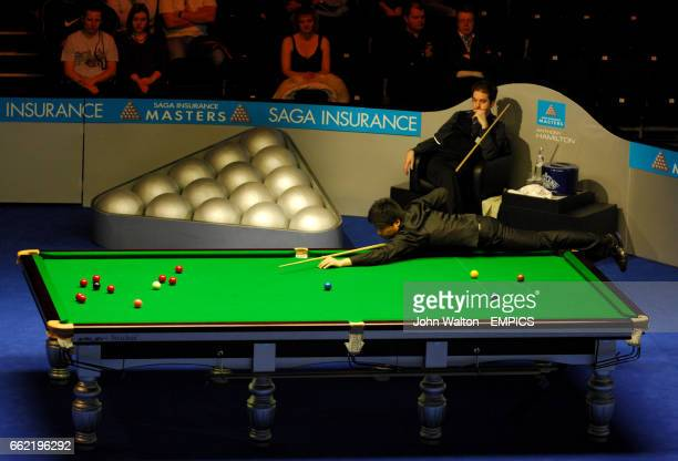 China's Ding Junhui pots the pick watched by Anthony Hamilton