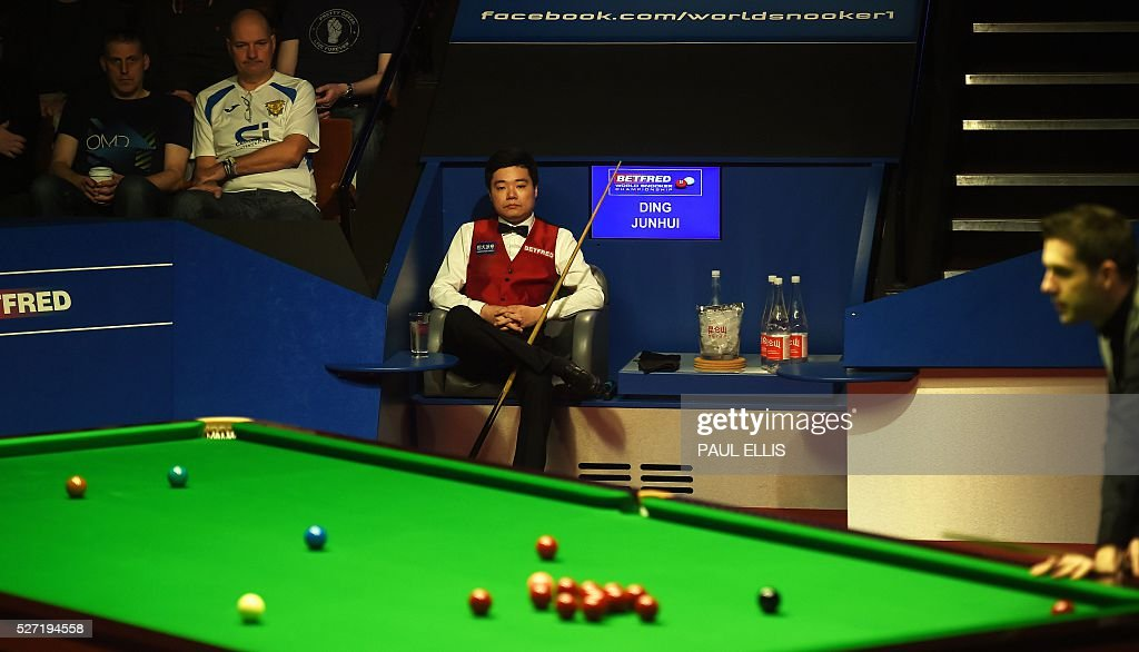 China's Ding Junhui watches as England's Mark Selby plays a shot during the third session of the World Snooker Final in Sheffield, northern England on May 2, 2016. / AFP / PAUL