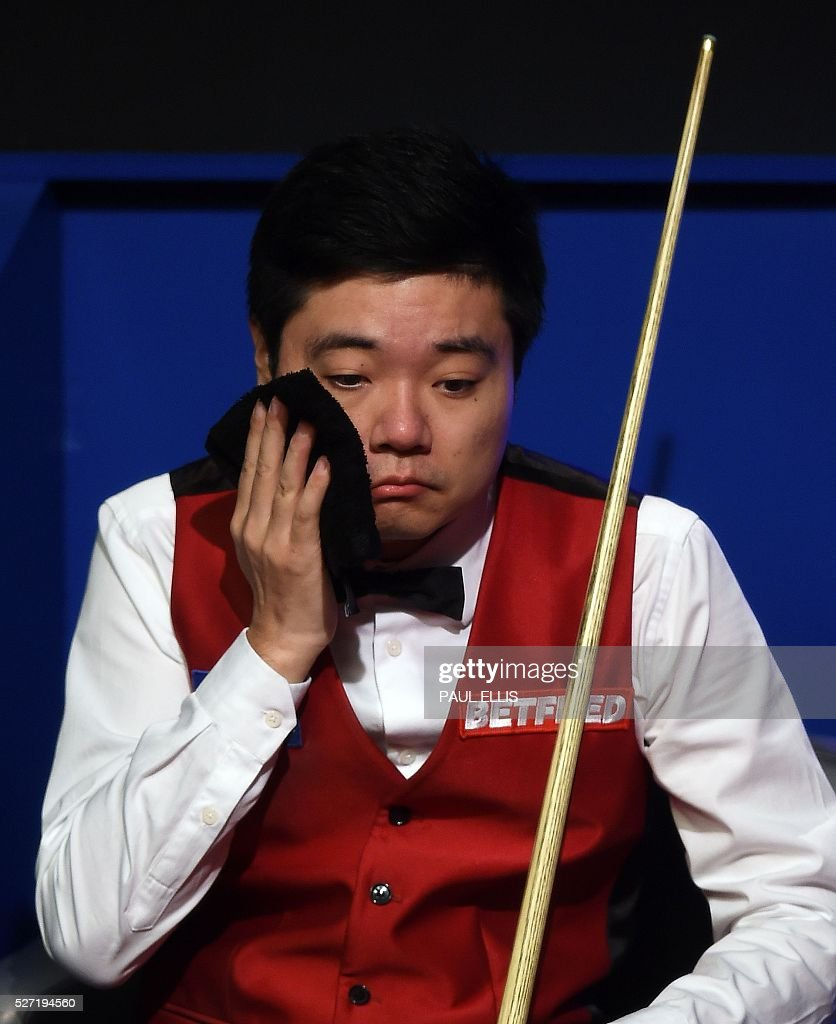 China's Ding Junhui wipes his face as England's Mark Selby plays a shot during the third session of the World Snooker Final in Sheffield, northern England on May 2, 2016. / AFP / PAUL