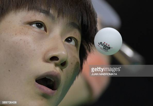 TOPSHOT China's Ding Ning eyes the ball as she serves in the women's team semifinal table tennis match against Singapore at the Riocentro venue...