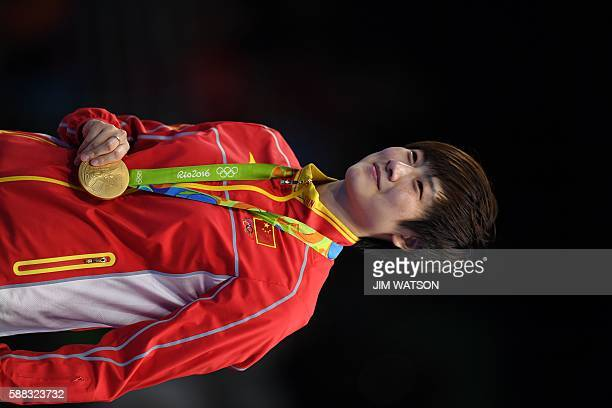 China's Ding Ning poses with her gold medal after beating China's Li Xiaoxia in their women's singles final table tennis match at the Riocentro venue...