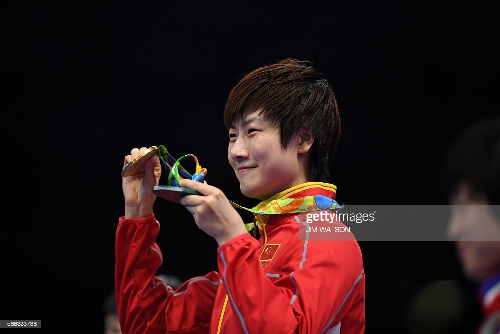 China's Ding Ning poses with her gold medal after beating China's Li Xiaoxia in their women's singles final table tennis match at the Riocentro venue during the Rio 2016 Olympic Games in Rio de Janeiro on August 10, 2016. / AFP / Jim WATSON