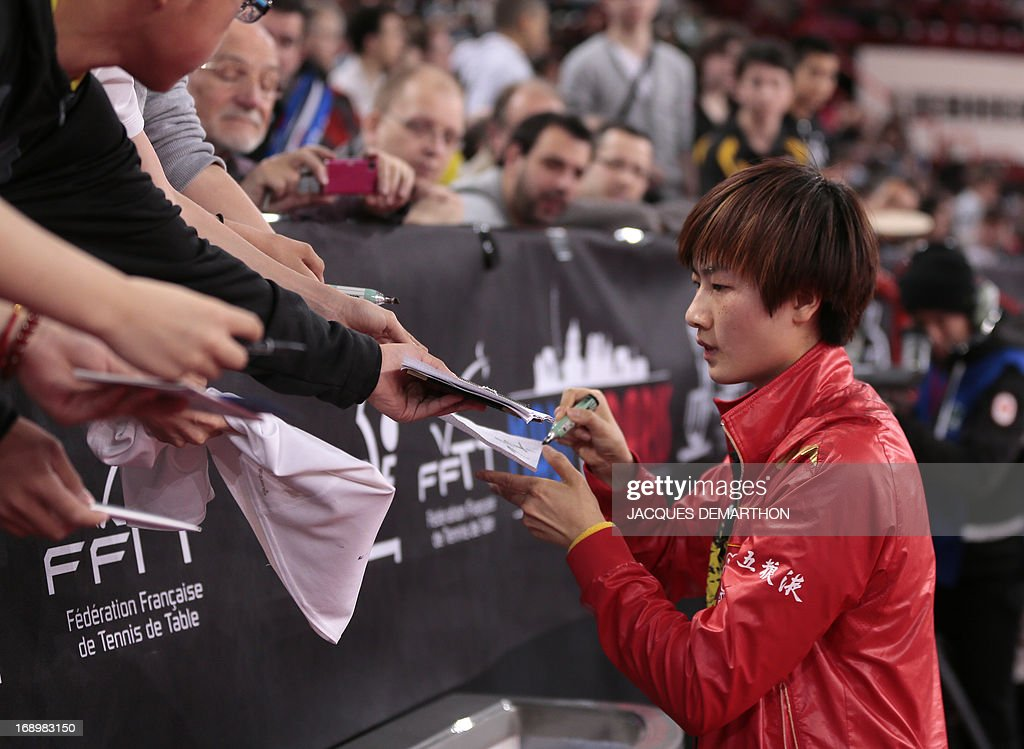 China's Ding Ning (R) signs autographs for fans after her victory over North Korea's on May 18, 2013 in Paris, during the quater-finals of the women's singles of the World Table Tennis Championships.
