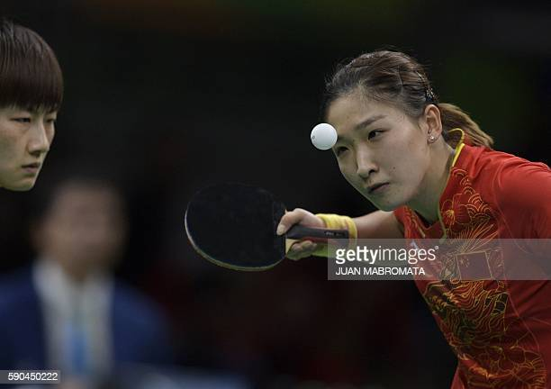 China's Ding Ning watches China's Liu Shiwen serve in the women's team gold medal final table tennis match against Germany's Xiaona Shan and...
