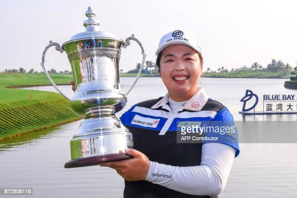 China's Feng Shanshan poses with the trophy after winning the Blue Bay LPGA golf tournament at Jian Lake Blue Bay Golf Course on China's southern...