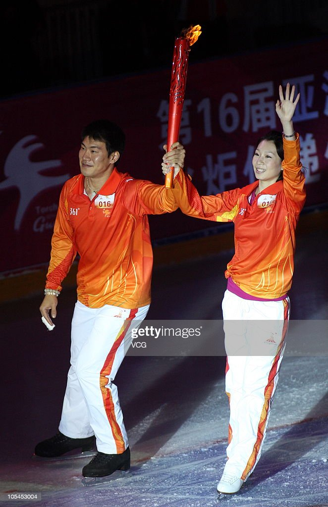 China's figure skaters <a gi-track='captionPersonalityLinkClicked' href=/galleries/search?phrase=Zhang+Dan&family=editorial&specificpeople=813902 ng-click='$event.stopPropagation()'>Zhang Dan</a>(R) and <a gi-track='captionPersonalityLinkClicked' href=/galleries/search?phrase=Zhang+Hao&family=editorial&specificpeople=813903 ng-click='$event.stopPropagation()'>Zhang Hao</a>(L) raise the torch during a 2010 Guangzhou Asian Games Torch Relay Ceremony at Harbin Baqu Stadium on October 14, 2010 in Harbin, Heilongjiang province of China.