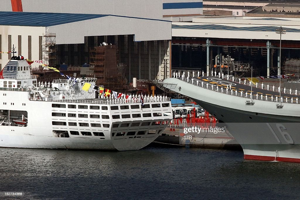 China's first aircraft carrier, the 'Liaoning' (R) sits berthed at the naval base in Dalian, northeast China's Liaoning province. China's first aircraft carrier, a former Soviet ship it bought from Ukraine and refurbished, entered service on September 25, the defence ministry in Beijing said. CHINA