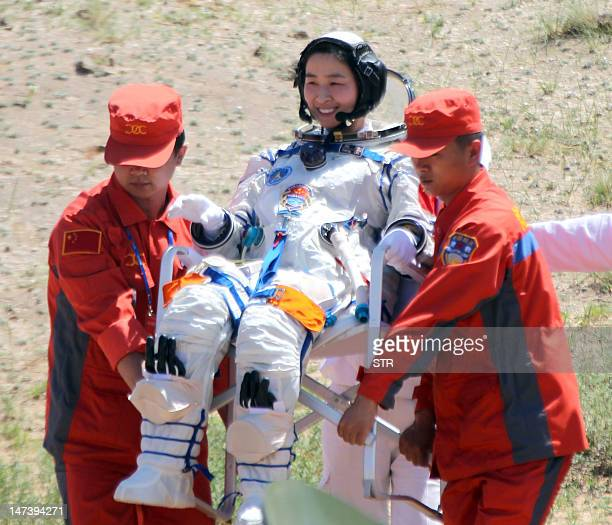 China's first female astronaut 33yearold Liu Yang gets carried by two retrieval crew members after she emerged from the charred returned capsule of...