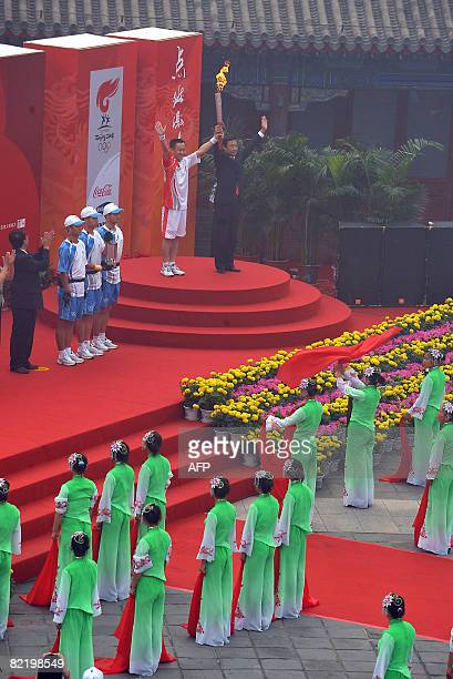 China's first man in space Yang Liwei holds up the Olympic torch as the day's first torchbearer to take the flame along a section of the Great Wall...