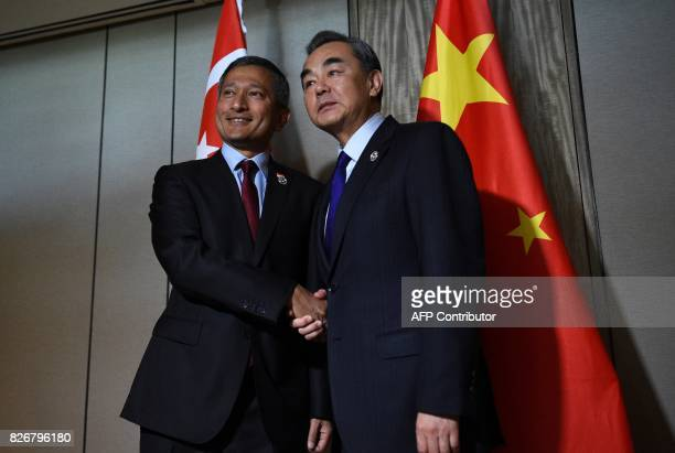 China's Foreign Minister Wang Yi shakes hands with his Singaporean counterpart Vivian Balakrishnan prior to their bilateral meeting on the sidelines...