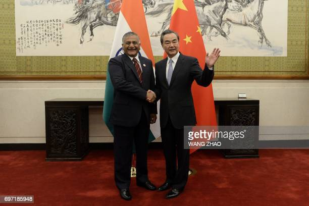 China's Foreign Minister Wang Yi shakes hands with India's Minister of State for External Affairs Vijay Kumar Singh at Diaoyutai State Guesthouse in...