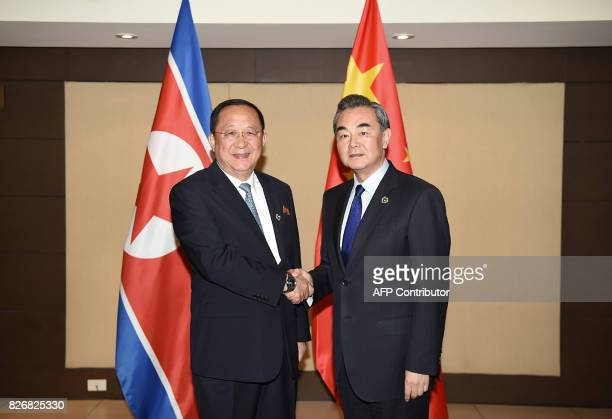 China's Foreign Minister Wang Yi shakes hands with North Korea's Foreign Minister Ri Yong Ho during their bilateral meeting on the sidelines of the...