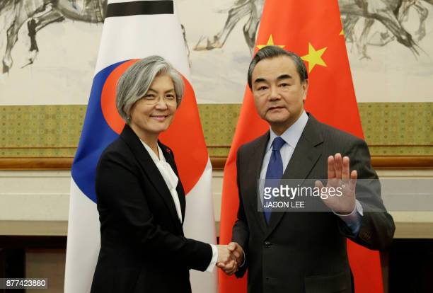 China's Foreign Minister Wang Yi shakes hands with South Korea's Foreign Minister Kang Kyungwha at the Diaoyutai State Guesthouse in Beijing on...